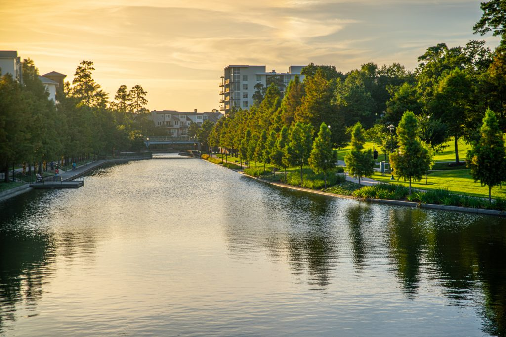 Woodlands Waterway at sunset with greenspace visible on either side of the water