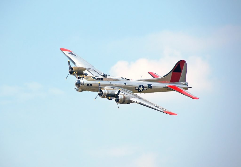 B-17 bomber from WWII era flying through blue skies. Visiting these planes is one of the most fun things to do in Conroe TX