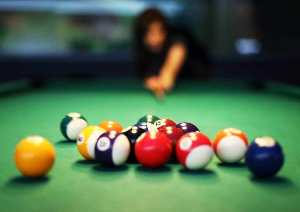 Woman breaking a group of billiard balls with the balls and green table in the foreground