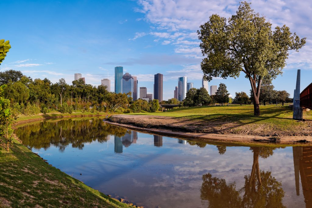 Buffalo Bayou park with water in the foreground and the skyline in the background. Some of the best hiking in Houston is at Buffalo Bayou Park!
