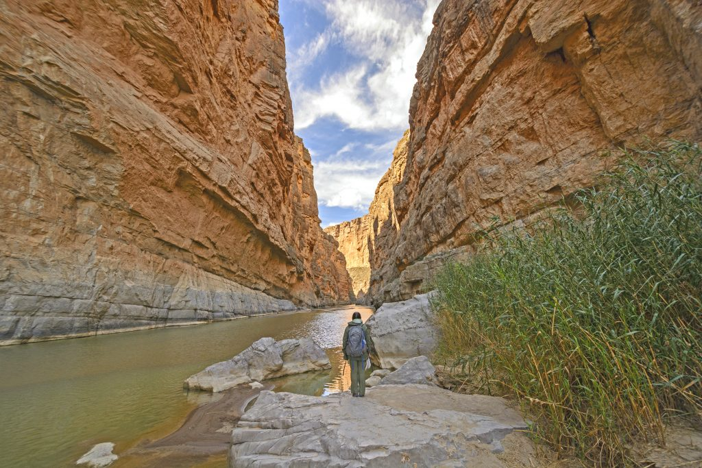 Hiker standing in Santa Elena Canyon in Big Bend National Park looking away from the camera