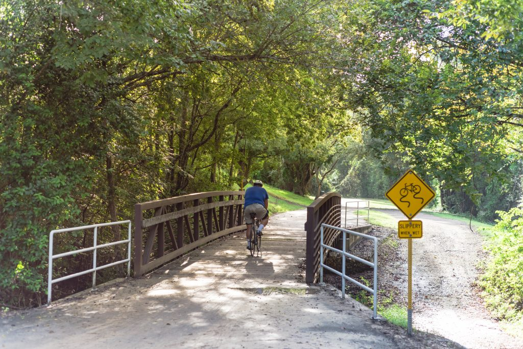 Man riding a bike over a small bridge on a trail in Houston TX