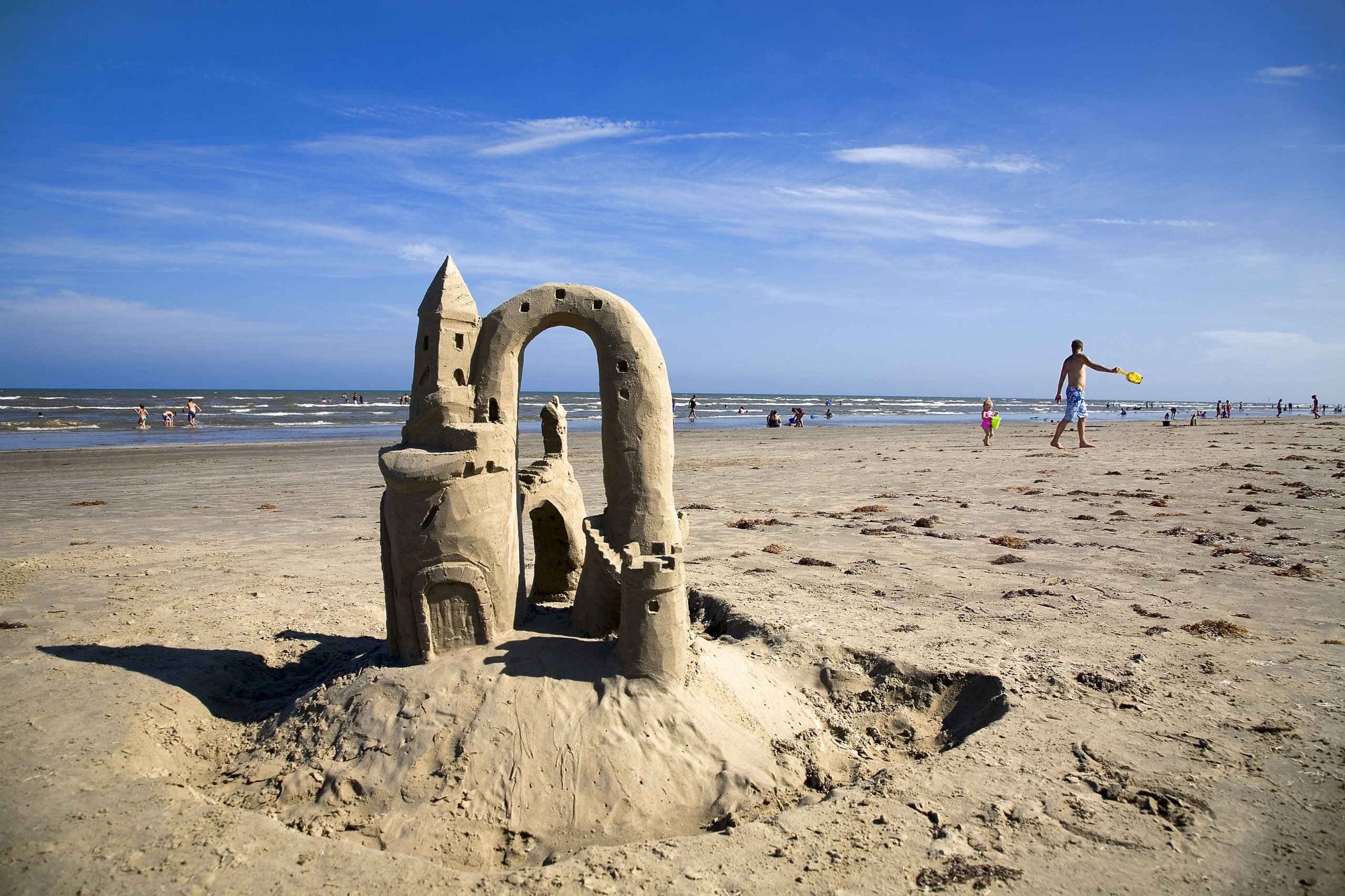 Small sandcastle on the Port Aransas beach with children playing in the background. port aransas is one of the best destinations for spring break in texas