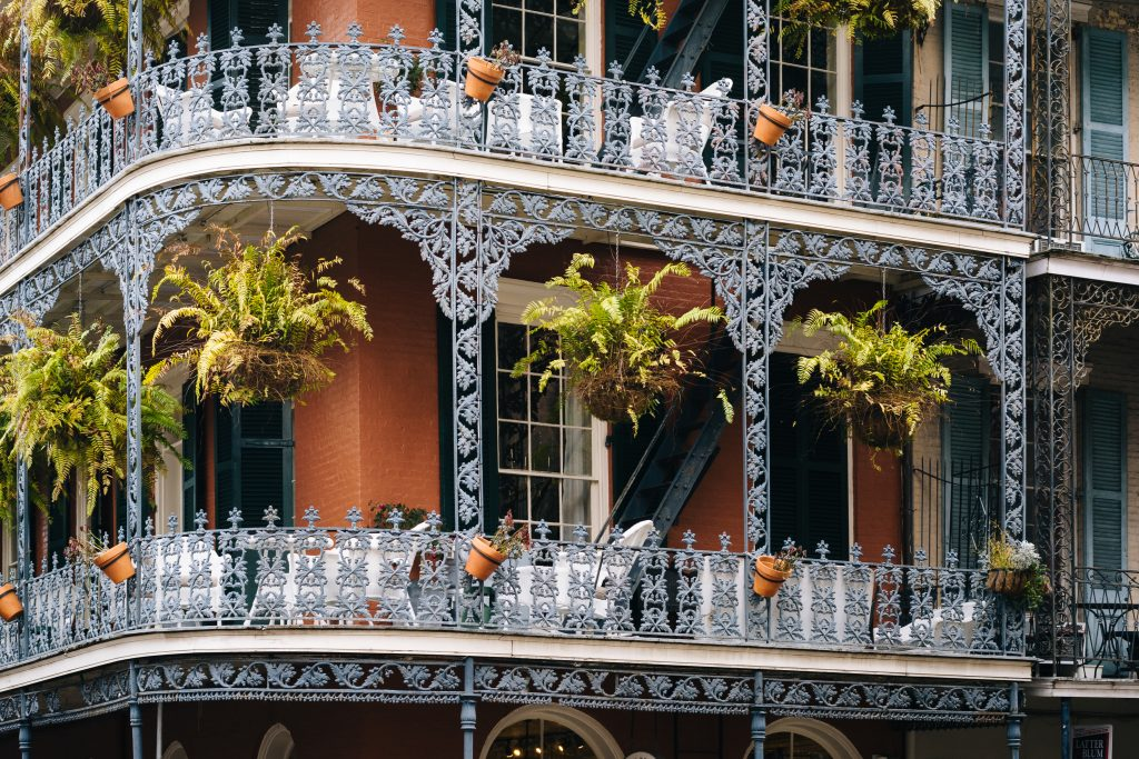 Red building in NOLA French Quarter with iron balconies and black shutters. NOLA is one of the best weekend trips from Austin Texas