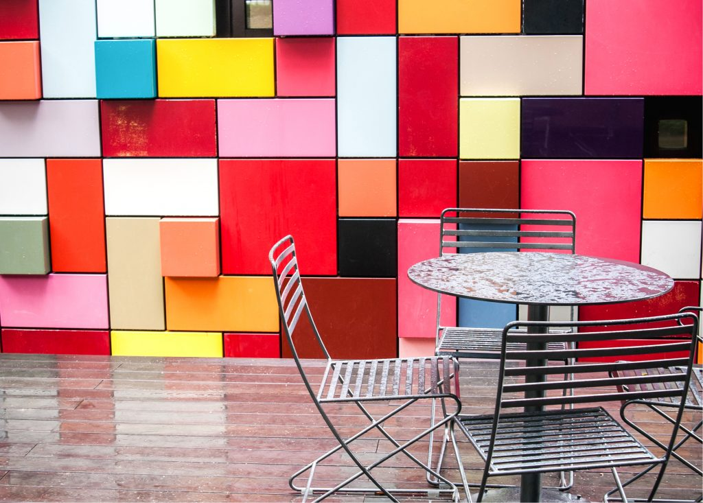 Small table with 4 chairs in front of a wall made of colored blocks in Discovery Green, one of the best houston photography locations