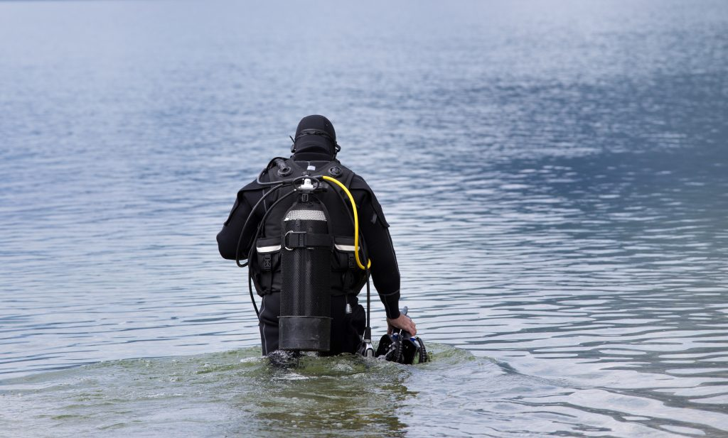 Scuba diver walking into lake to start a dive, facing away from the camera. Scuba diving definitely belongs on any divers list of what to do in canyon lake tx