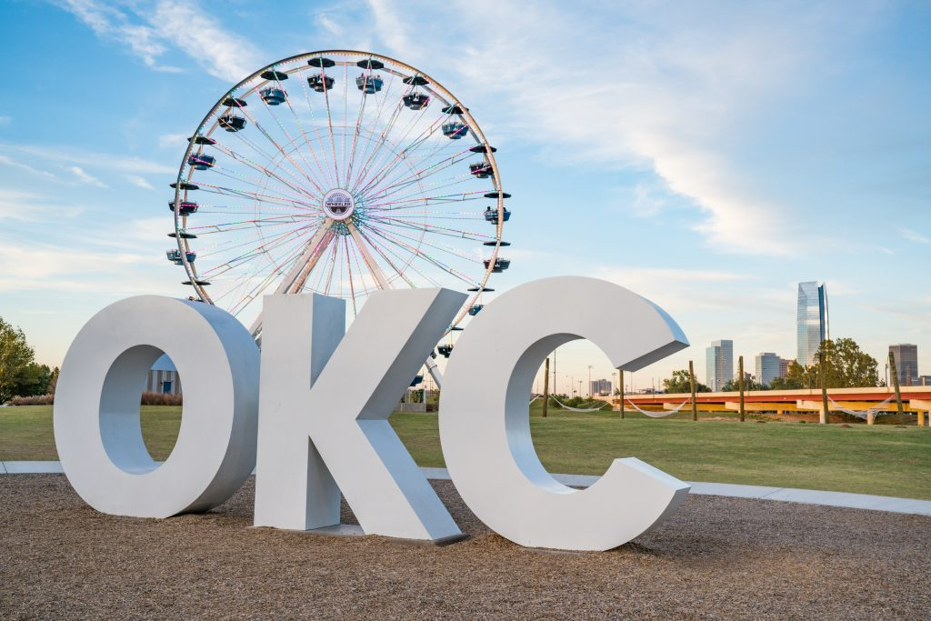 White lettering spelling out OKC in the foreground with a Ferris wheel in the background in OKC