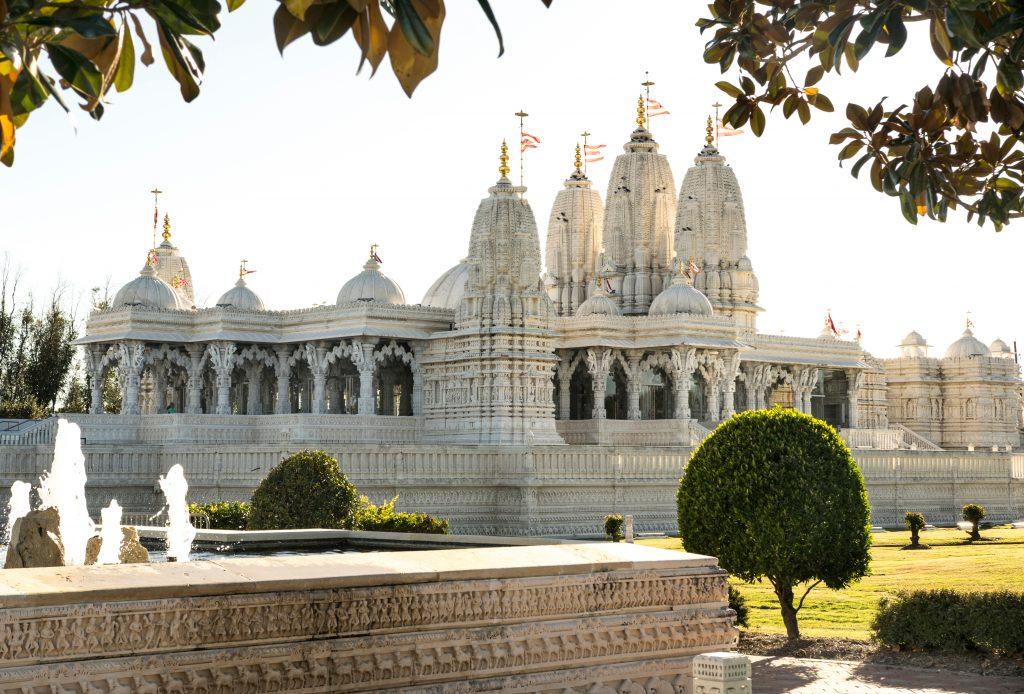 BAPS Shri Swaminarayan Temple as seen from the side with leaves in the foreground. This traditional Hindu temple is one of the most instagrammable places in Houston Texas
