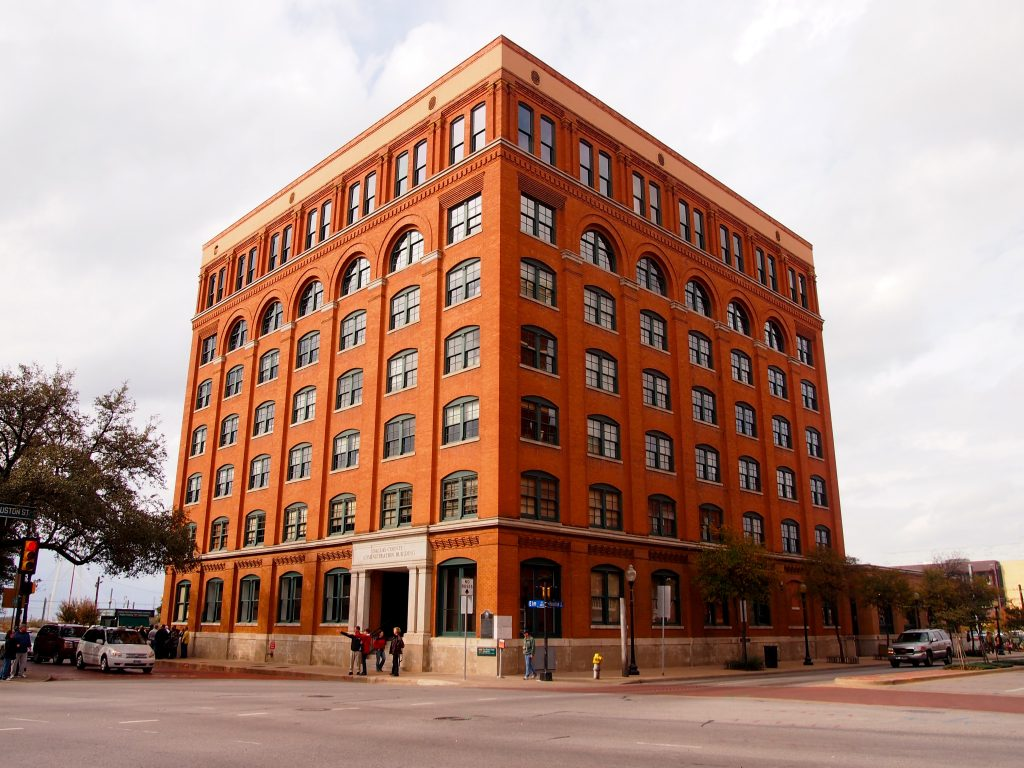 Exterior of the red brick building that houses the 6th Floor Museum in Dallas Texas