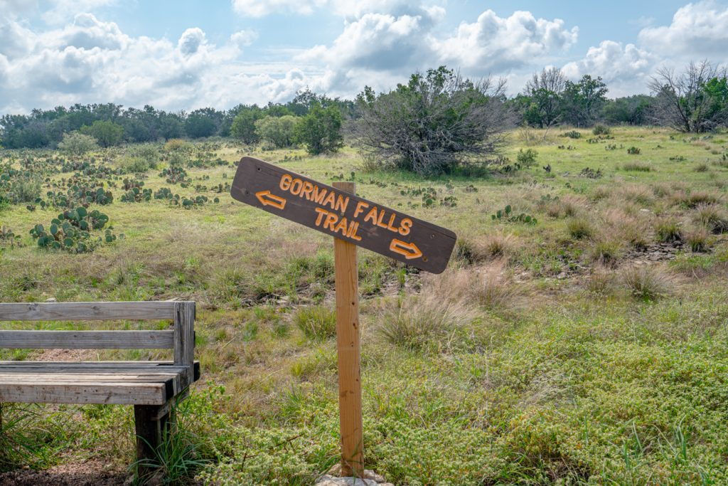 "Brown sign with yellow lettering that reads ""gorman falls trail"" with a central texas landscape behind it"