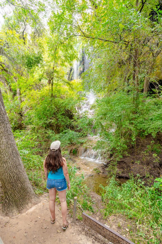 kate storm standing in front of gorman falls in colorado bend, one of the best texas state parks in hill country