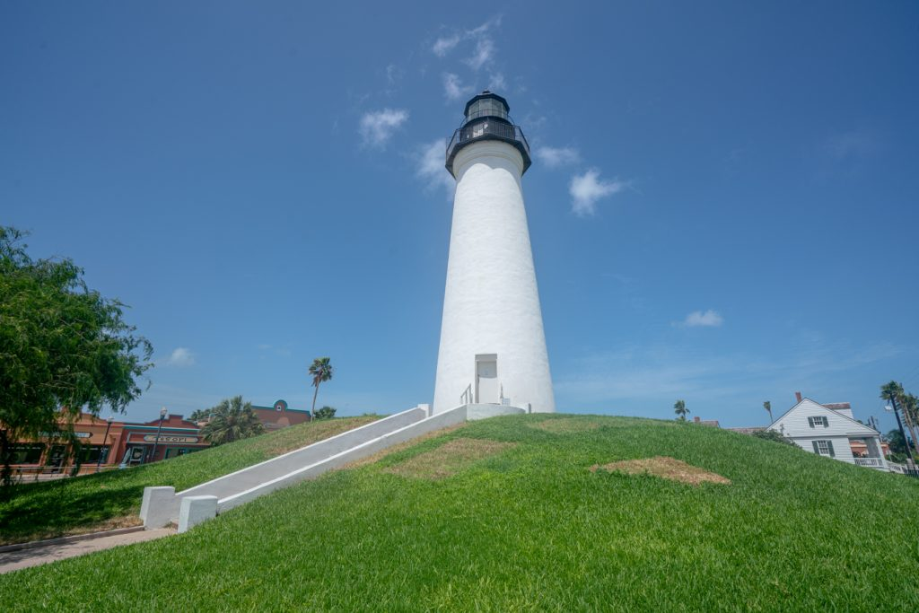 White Port Isabel lighthouse at the top of a small hill covered in a green lawn, one of the best things to do in port isabel texas