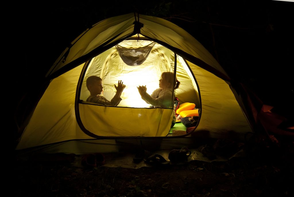 Two children playing in a yellow tent at night, with a light inside the tent illuminating them