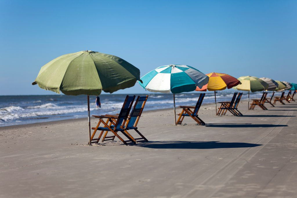 beach chairs with corresponding colorful umbrellas set up on the sand at one of the beaches in galveston texas