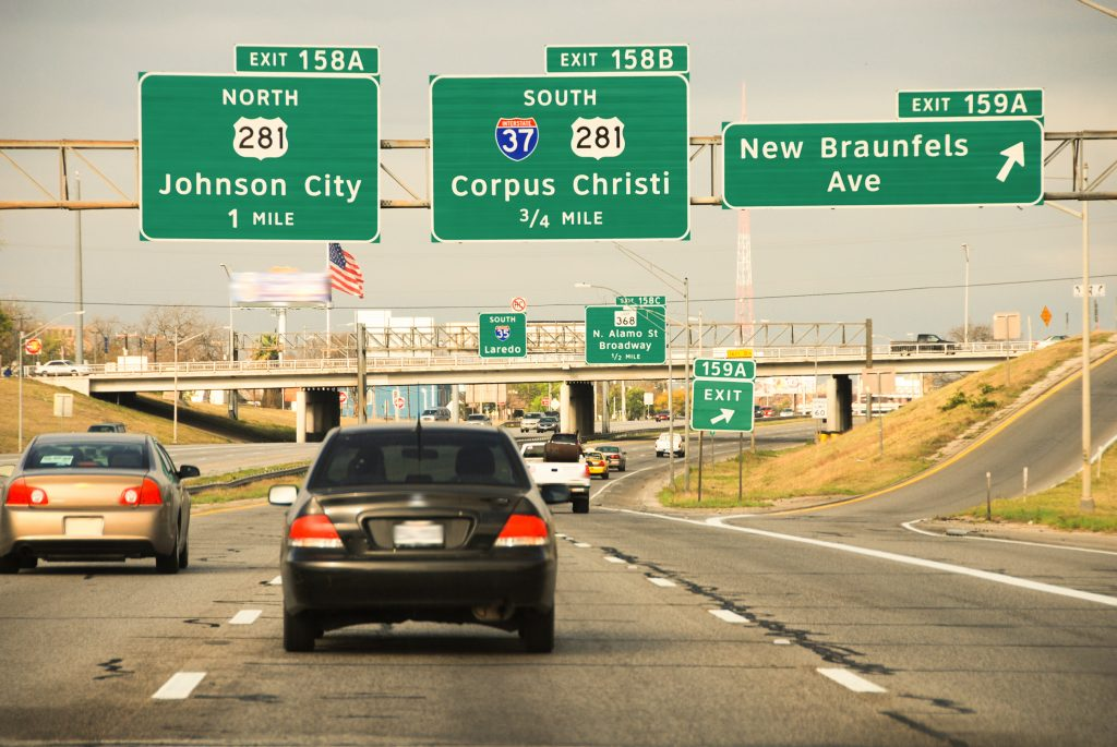 interstate view when driving from austin to san antonio with signs for 281 in the image and a black compact car in the foreground