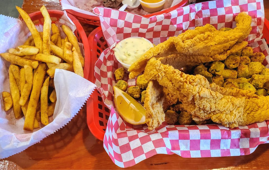 Basket of fried fish with a basket of french fries next to it. eating fried fish belongs on your list of what to do on south padre island texas