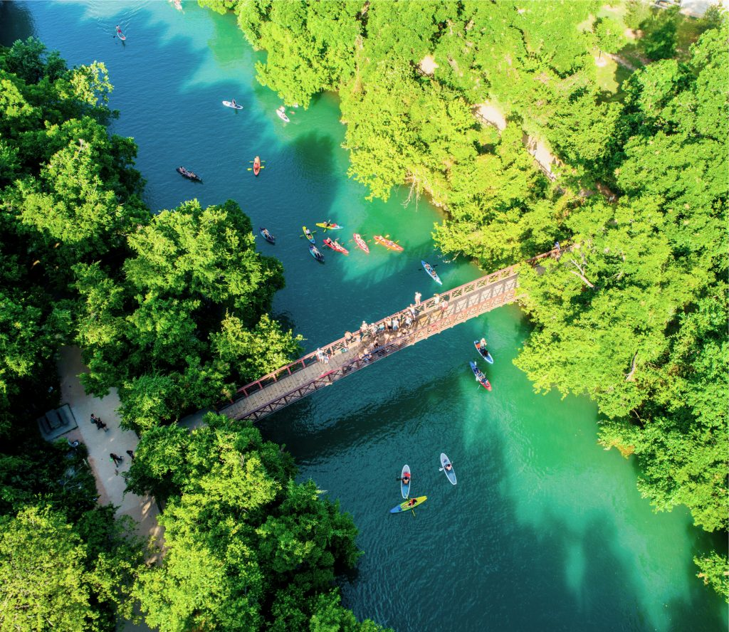 SUP paddlers on Lady Bird Lake as seen from above with a drone. A bridge crosses the lake in the center of the shot