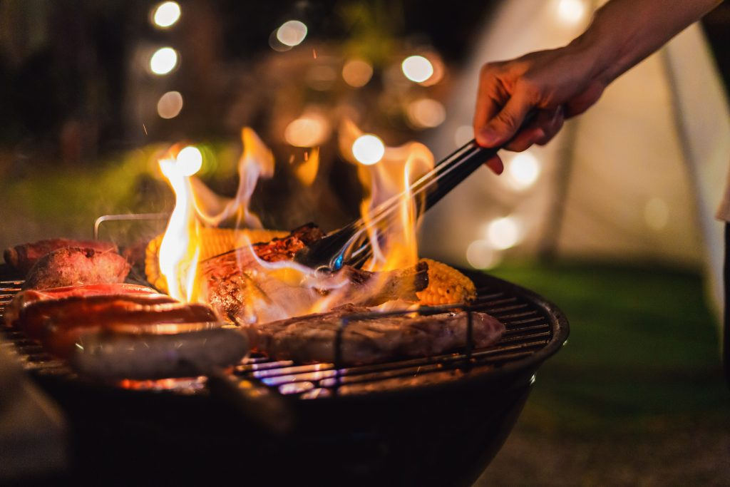 Outdoor grill at a campsite with sausagse on top and a hand holding tongs extended toward them