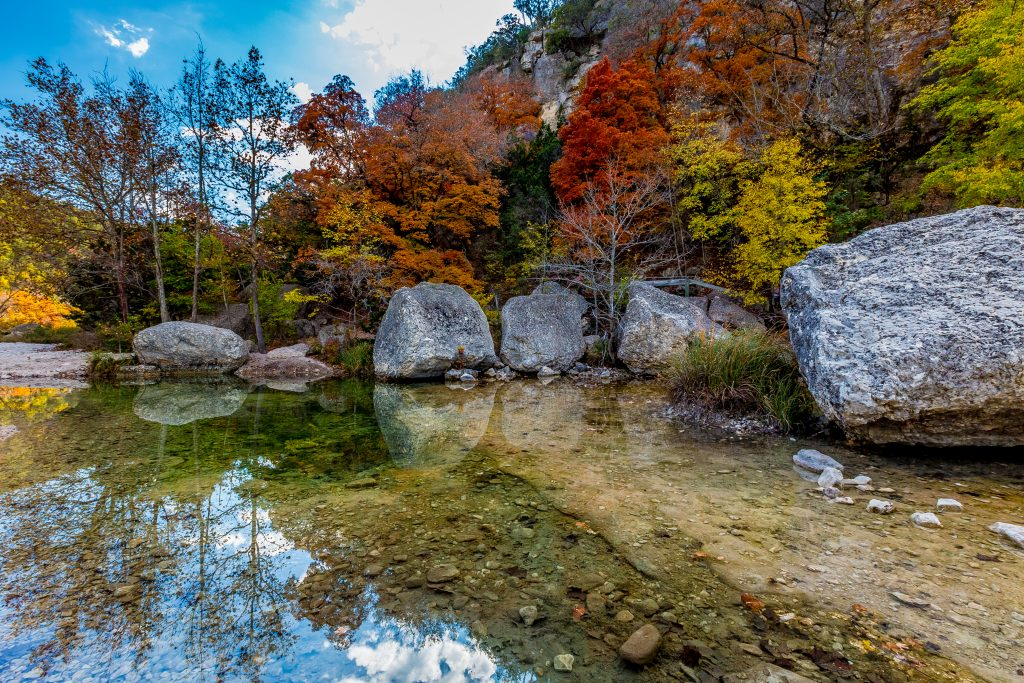 clear sabinal river in lost maples state natural area framed by fall foliage, home to one of the best hikes in texas