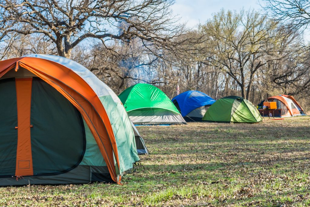 Collection of colorful tents set up and surrounded by trees at one of the campsites near dallas tx