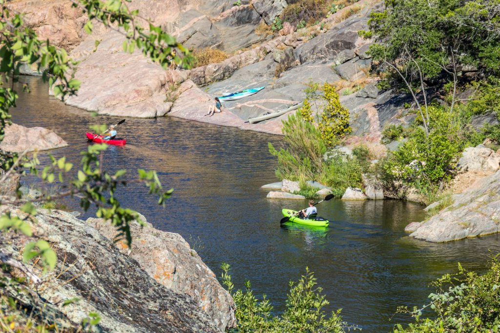 Kayakers in a rocky part of Inks Lake, one of the best places to camp near austin tx