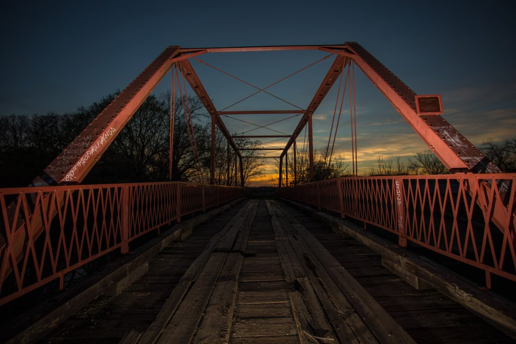 Old Alton Bridge in Denton Texas at sunset, with the red iron bars of the bridge in the foreground