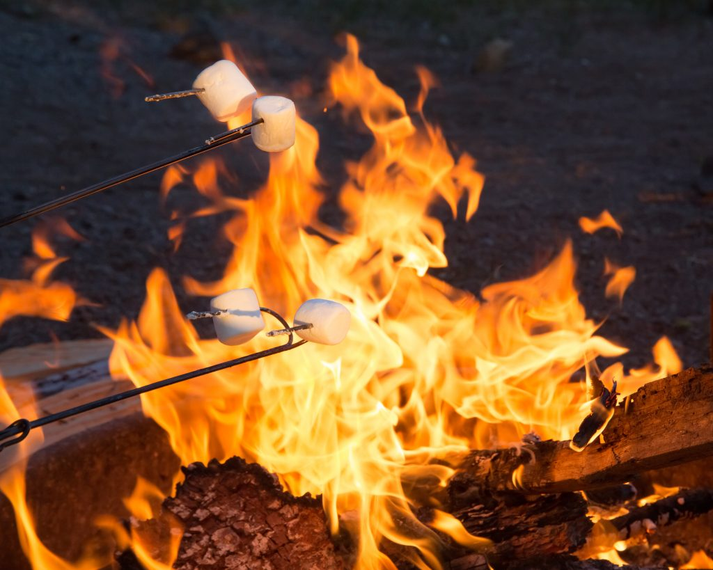 4 marshmallows roasting over an open campfire