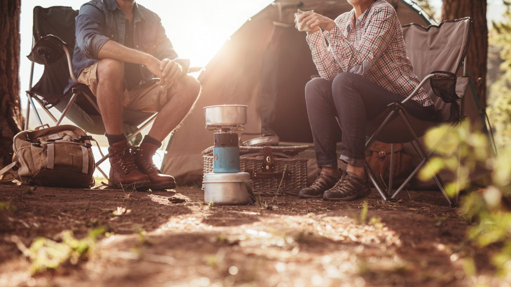 two people sitting in folding chairs at a campsite drinking coffee with a thermos between them