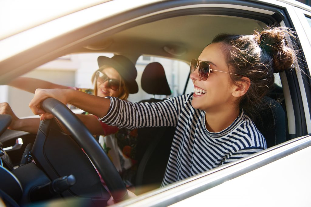 two young women in sunglasses sitting in a car on a road trip, one is leaning out the window slightly while driving