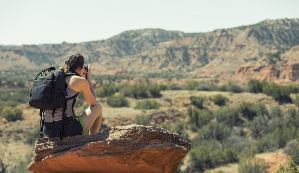 woman sitting on a rock wearing a black backpack and snapping a photo of a canyon when hiking in texas
