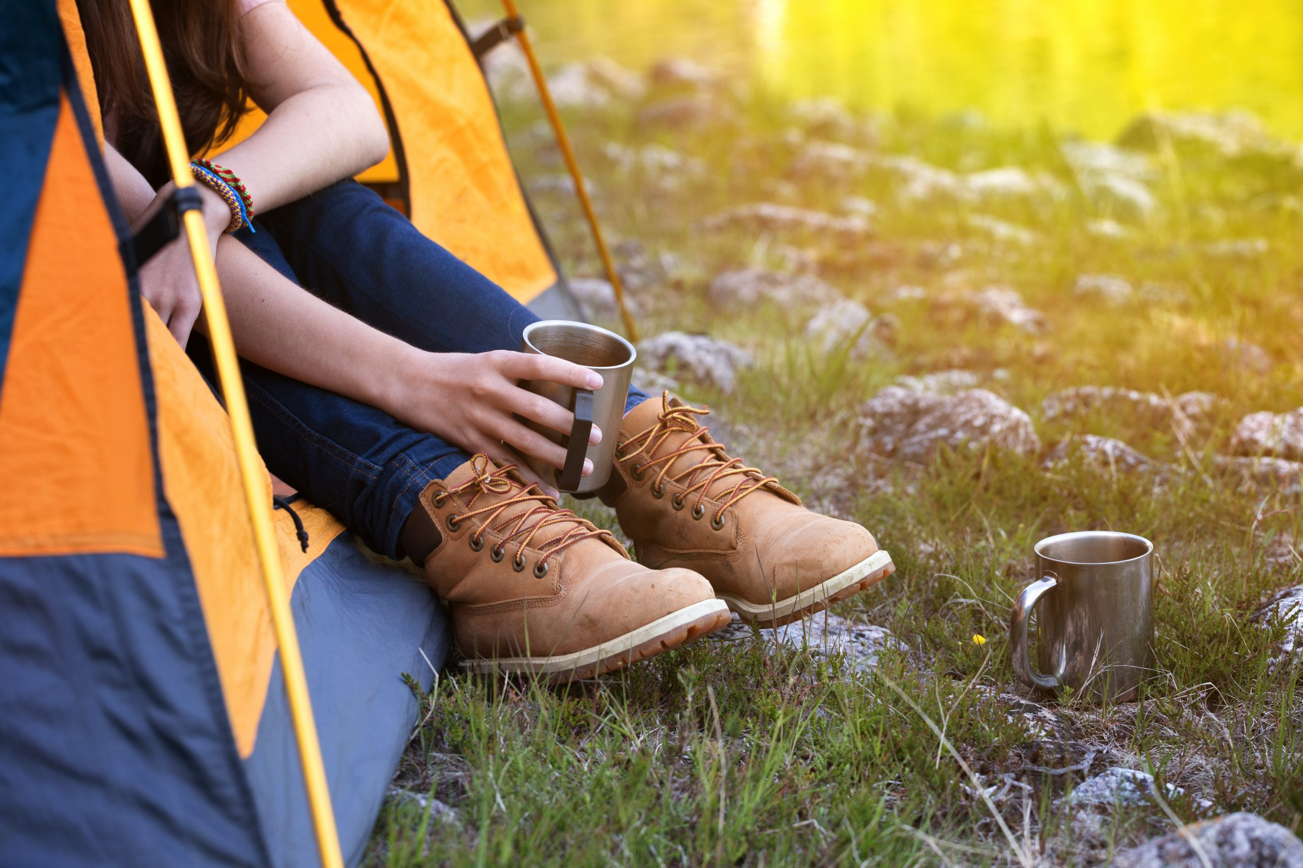 Young woman wearing lace up boots holding a coffee cup out of a yellow tent. Mornings like this are why to seek out the best camping near dallas tx!