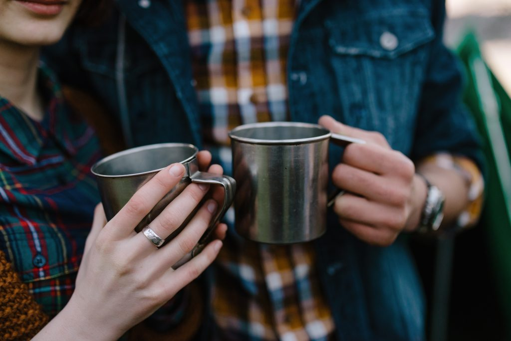 closely cropped photo of a couple in flannel shirts each holding a silver camping mug