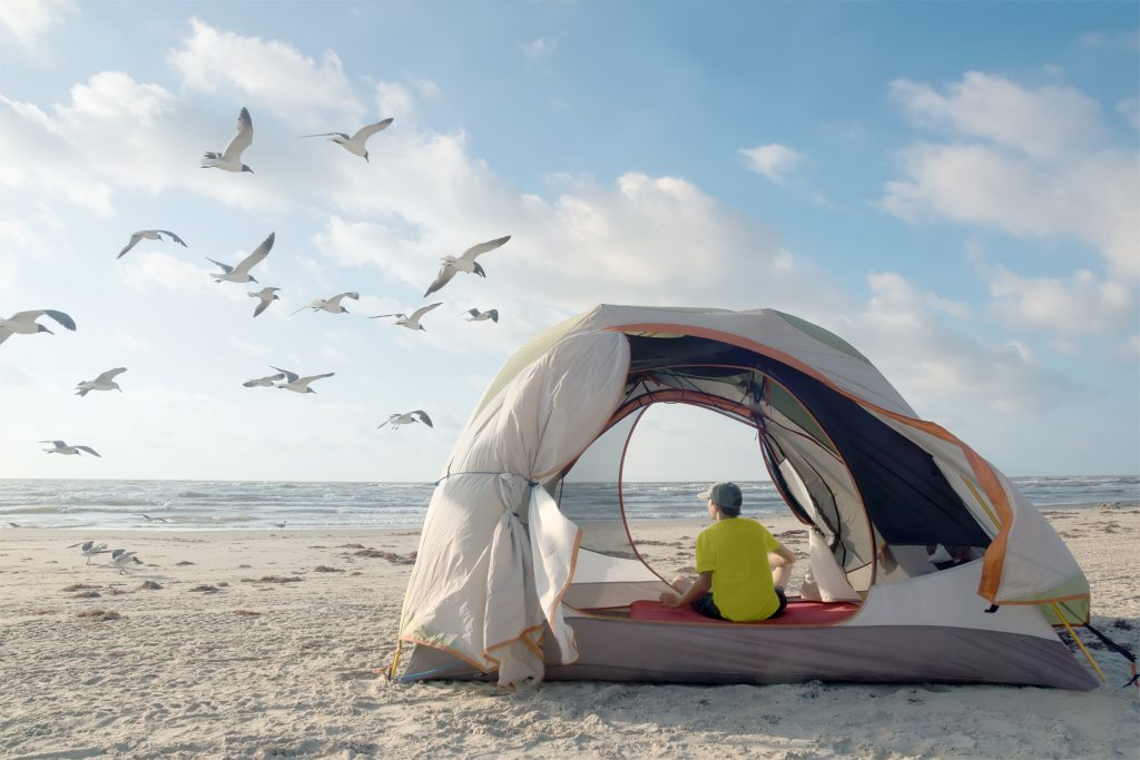 Man camping on the beach in an open tent with seagulls flying nearby in a state park near houston texas