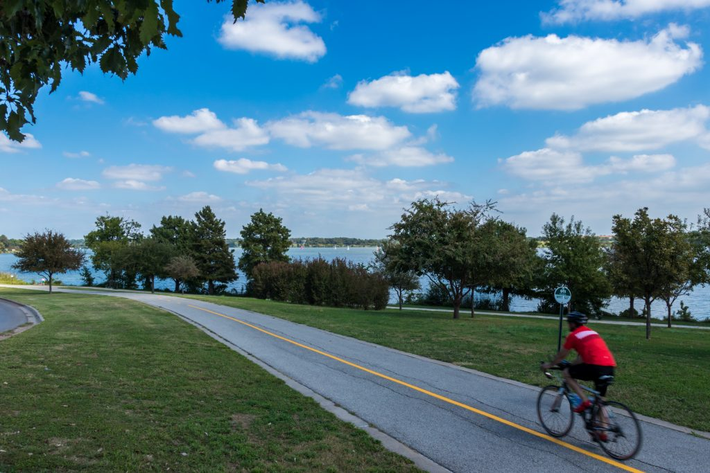 Man in a red shirt cycling along white rock lake trail, one of the best hiking trails in dallas tx