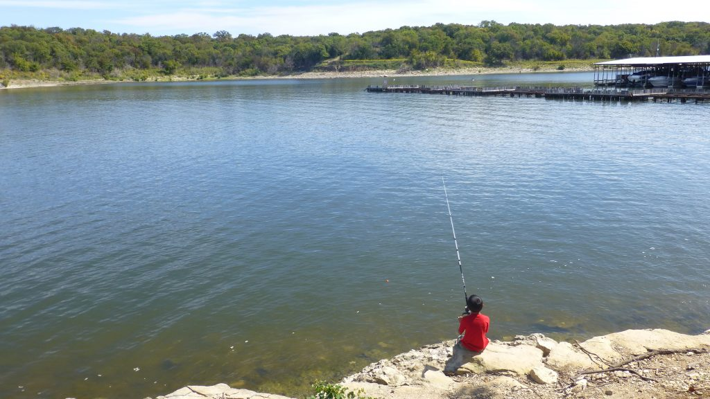 Child in a red shirt fishing on the shores of lake texoma, one of the most popular lakes in texas