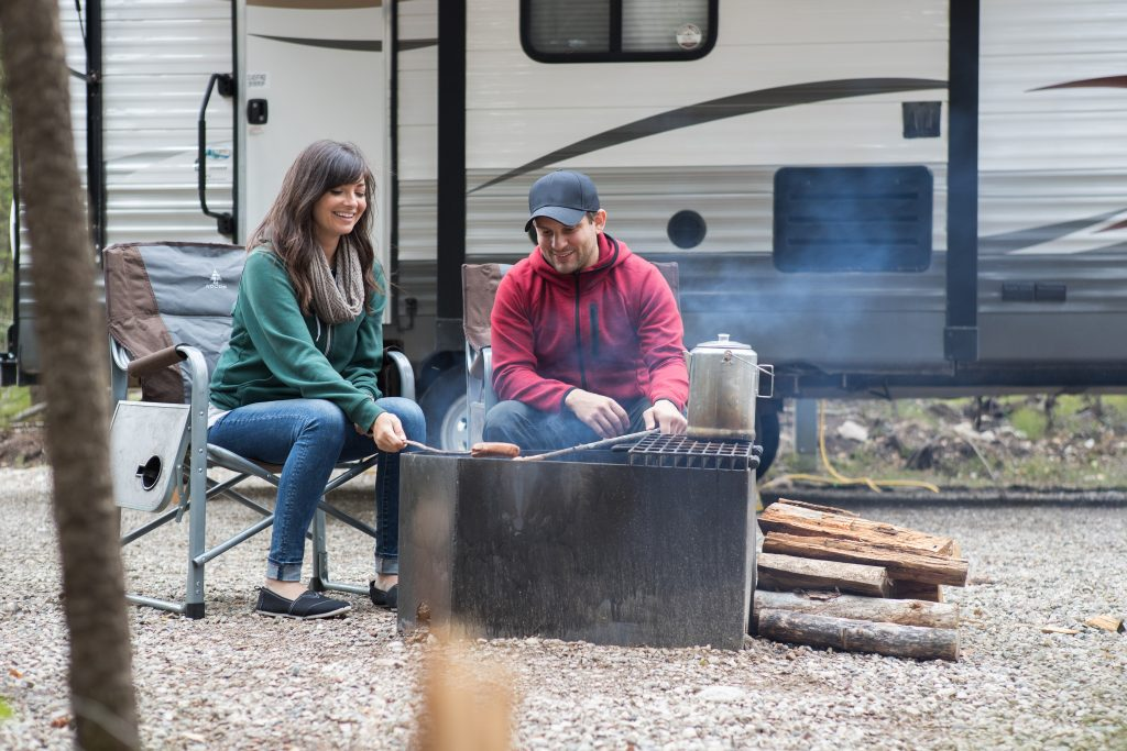 Couple sitting outside an RV at a campsite