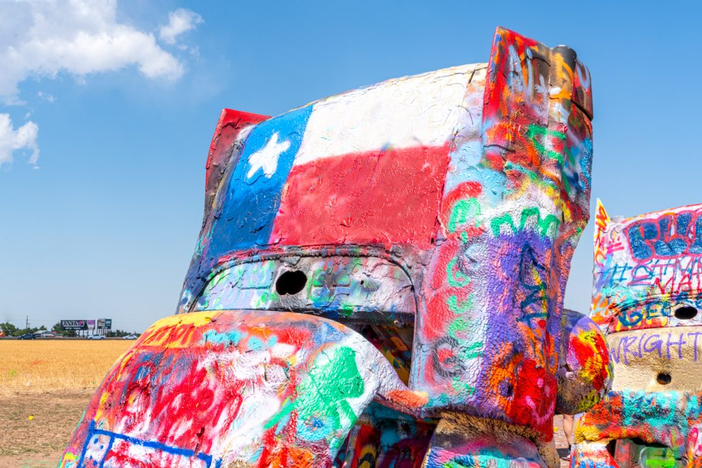Close up of a painted car at Route 66 Cadillac Ranch with a Texas flag on the bumper
