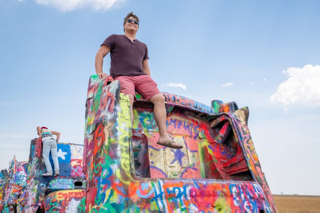 Jeremy Storm sitting on top of a car at Cadillac Ranch, one of the best Route 66 attractions in Texas