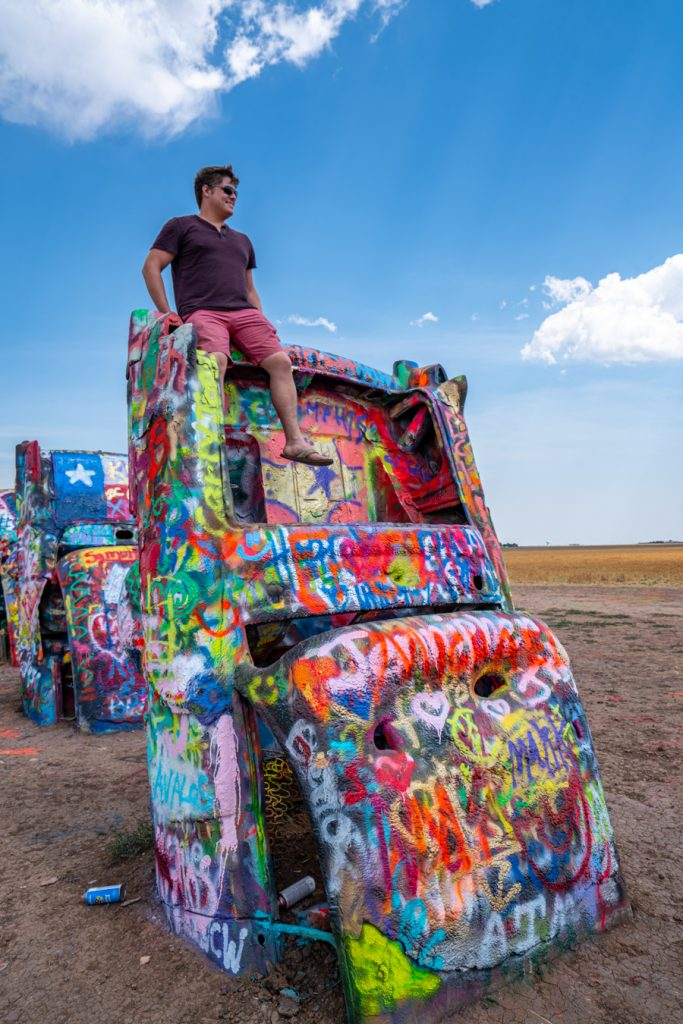Jeremy Storm sitting on top of a spraypainted Cadillac at Cadillac Ranch Amarillo Texas