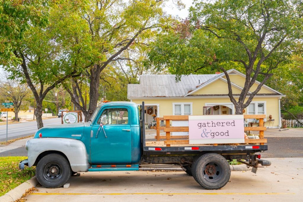 antique truck with turquoise cab parked in front of an antique shop. antiquing is one of the most fun things to do in fredericksburg tx