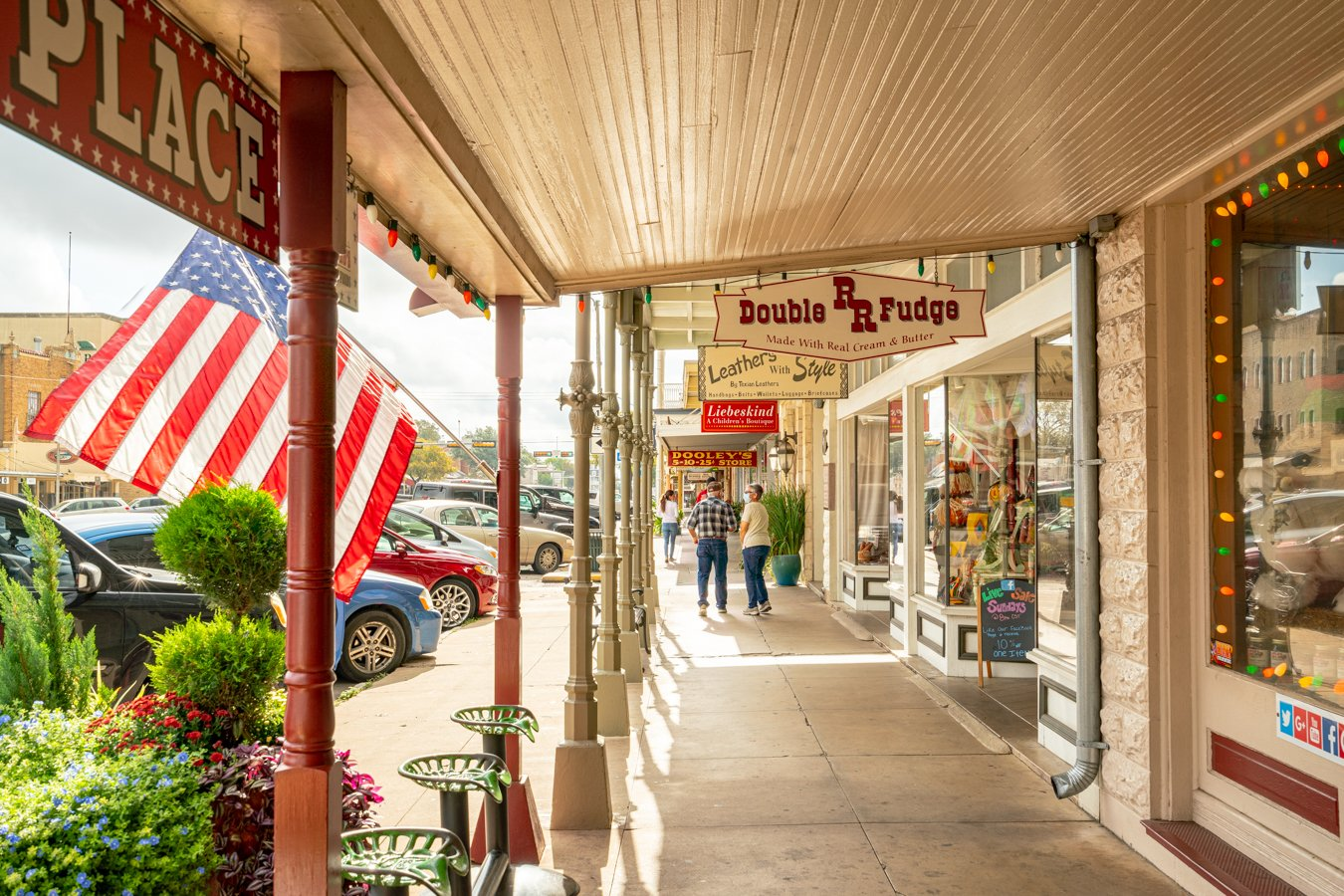 signs for shops along main street with an american flag blowing. visiting main street is one of the best things to do in fredericksburg tx