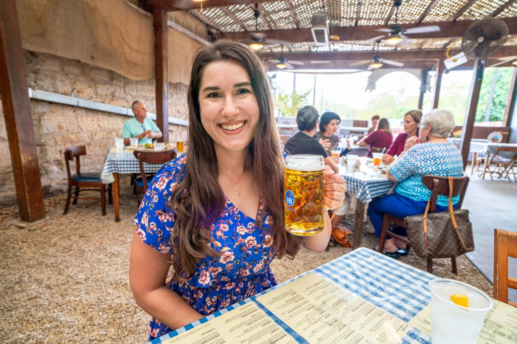 Kate Storm in a blue dress holding a beer stein in the auslander, which serves up some of the best german food in fredericksburg tx