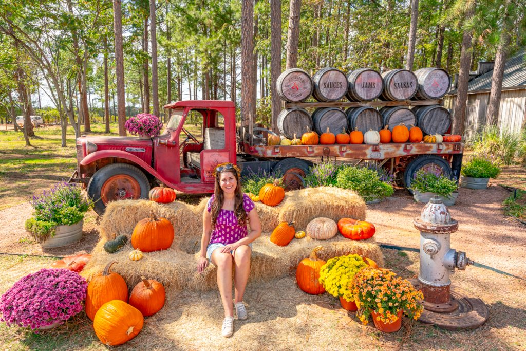 Kate Storm sitting surrrounded by pumpkins in front of an antique red truck at das peach haus in fredericksburg tx