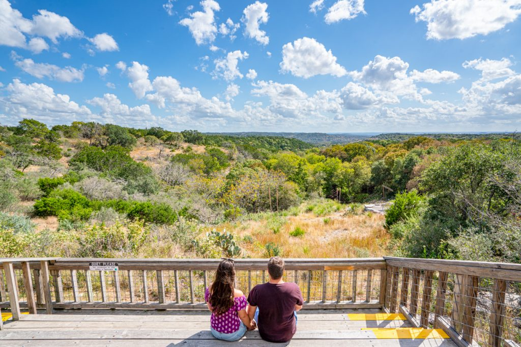 Kate Storm and Jeremy Storm overlooking the texas hill country on a wooden platform at old tunnel state park