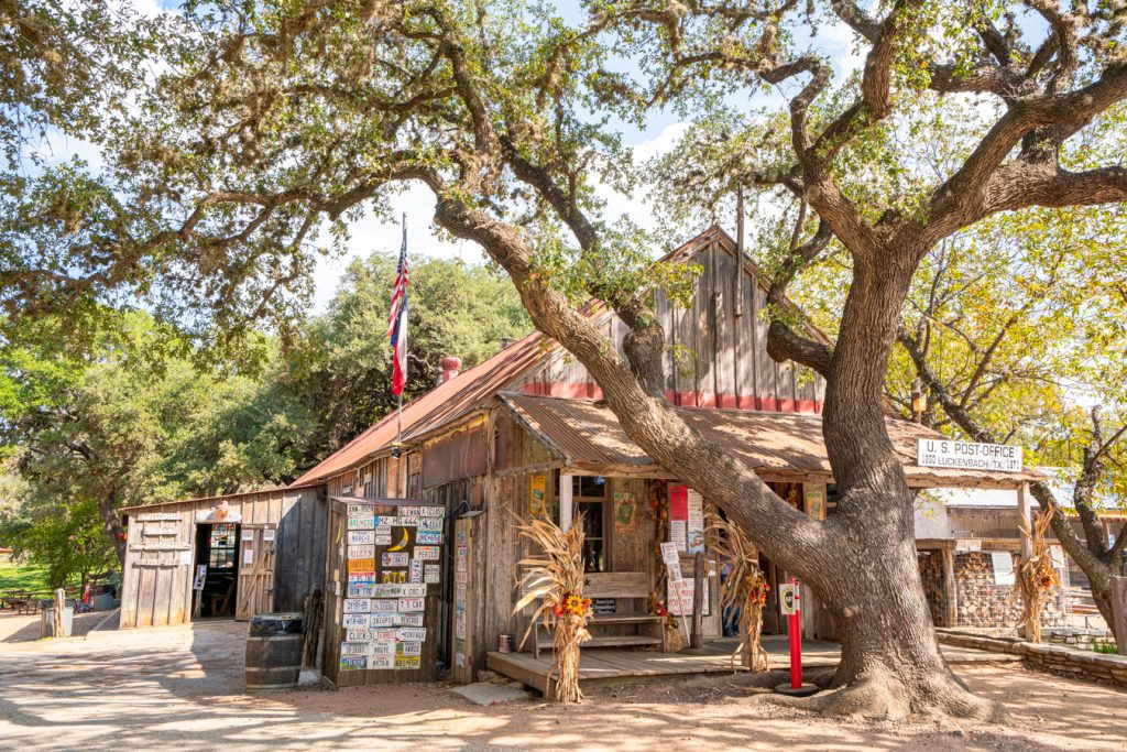 view of the front facade of the luckenbach post office as seen from an angle, one of the best things to see in luckenbach tx