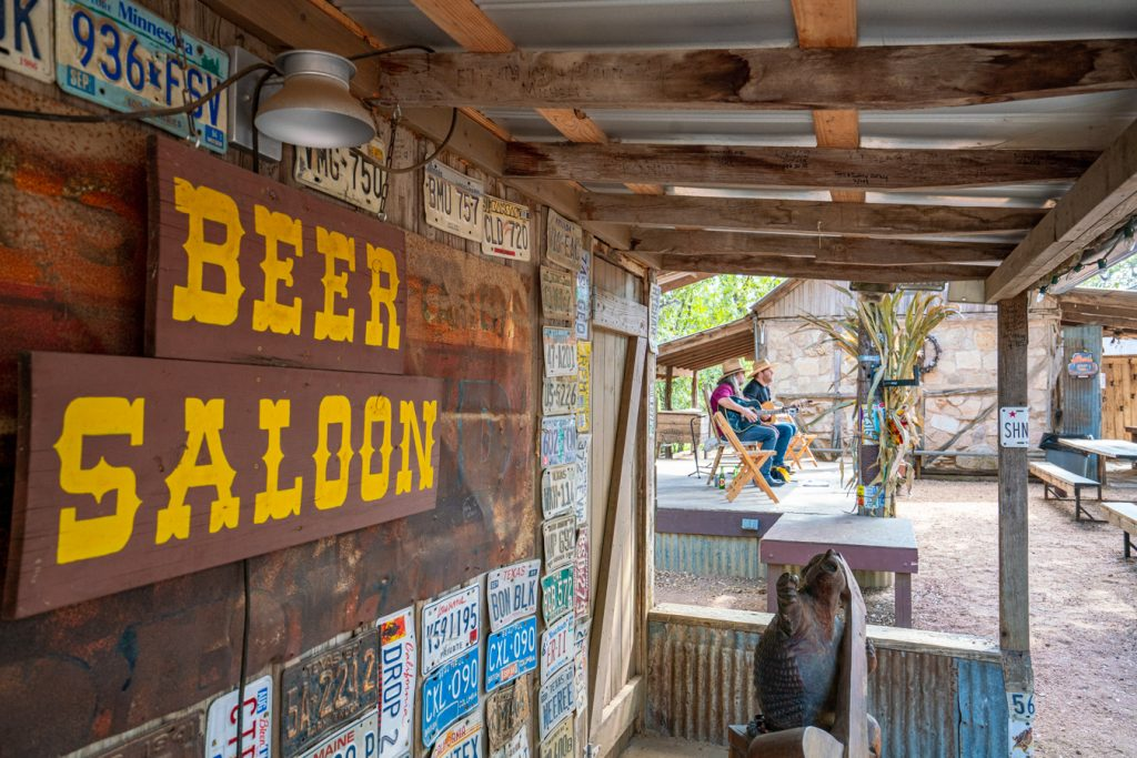 "decorated ""beer saloon"" sign in luckenbach tx with live performers in the background. live music is among the best things to do in luckenbach texas"