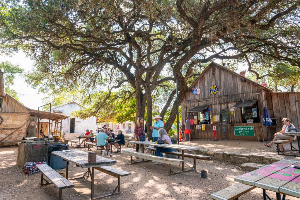 small crowd of people listening to live music in luckenbach texas from picnic tables under oak trees