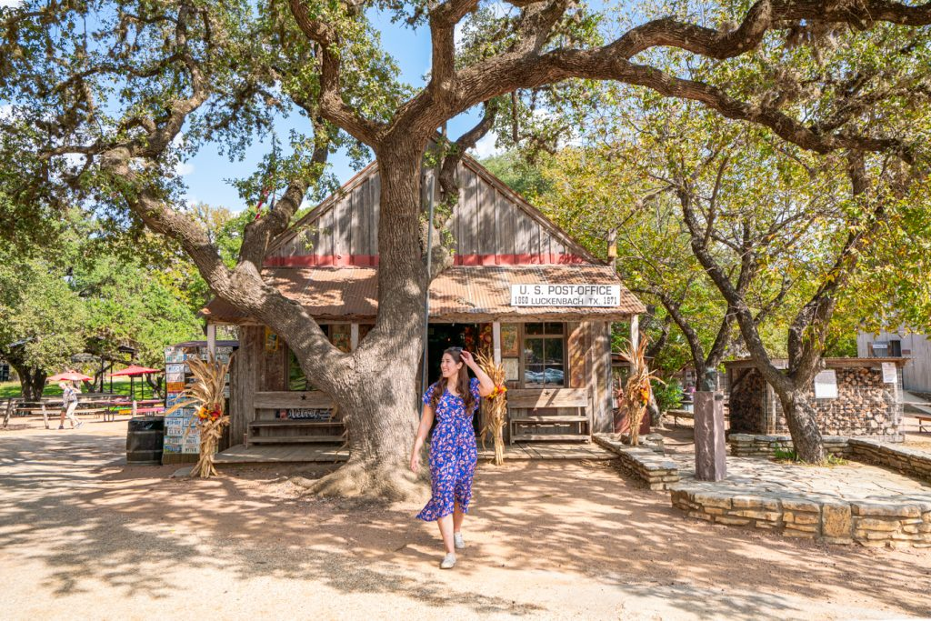Kate Storm in front of the former post office of luckenbach texas, one of the best things to see in luckenbach