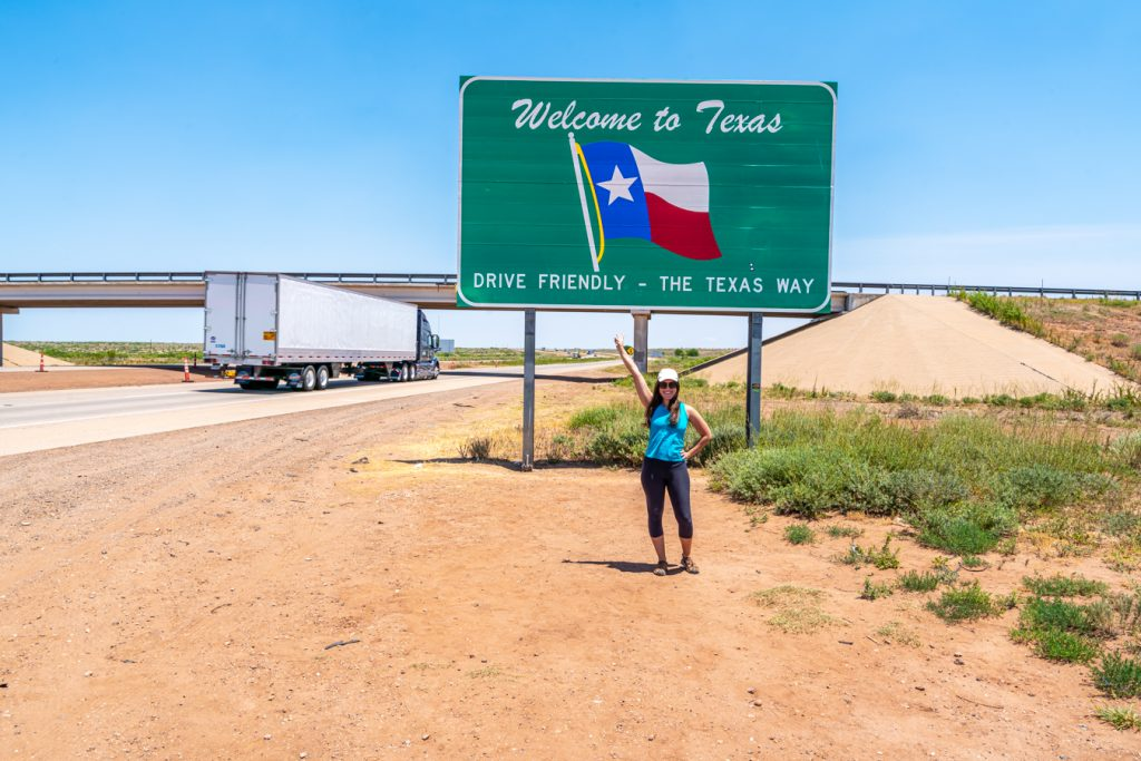 Kate Storm standing in front of the welcome to texas sign along i-40, which replaced historic route 66 tx