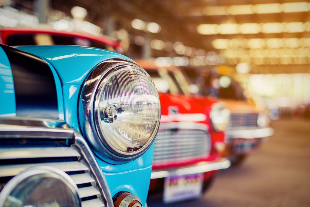 line of classic american cars with the headlight of a blue car in the foreground